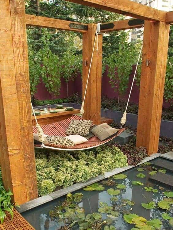 Outdoor Daybeds like this Asian-inspired design with a swinging hammock, koi pond and beautiful plants that surround a minimalist, sturdy frame make for a peaceful setting.